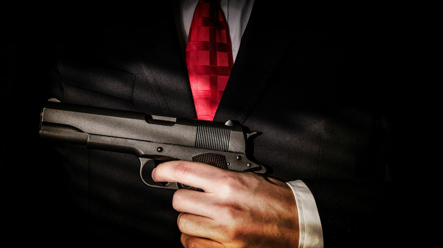 Mafioso holds pulled out gun, isolated on dark background   No Free Man Shall Ever Be Debarred The Use Of Arms ~ Jefferson   Featured