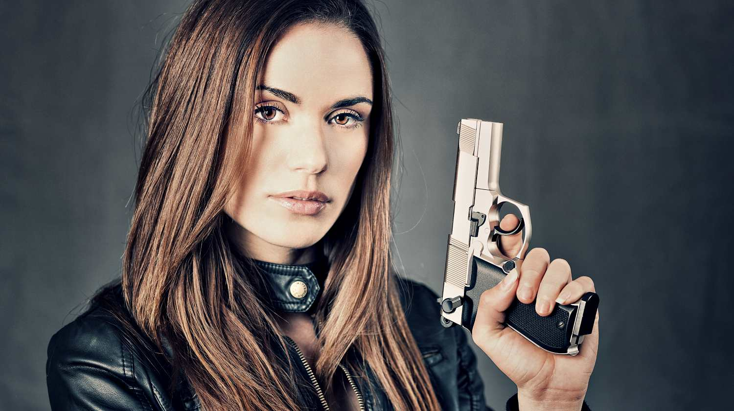 Feature | Woman with handgun | Best Guns for Women Living Alone