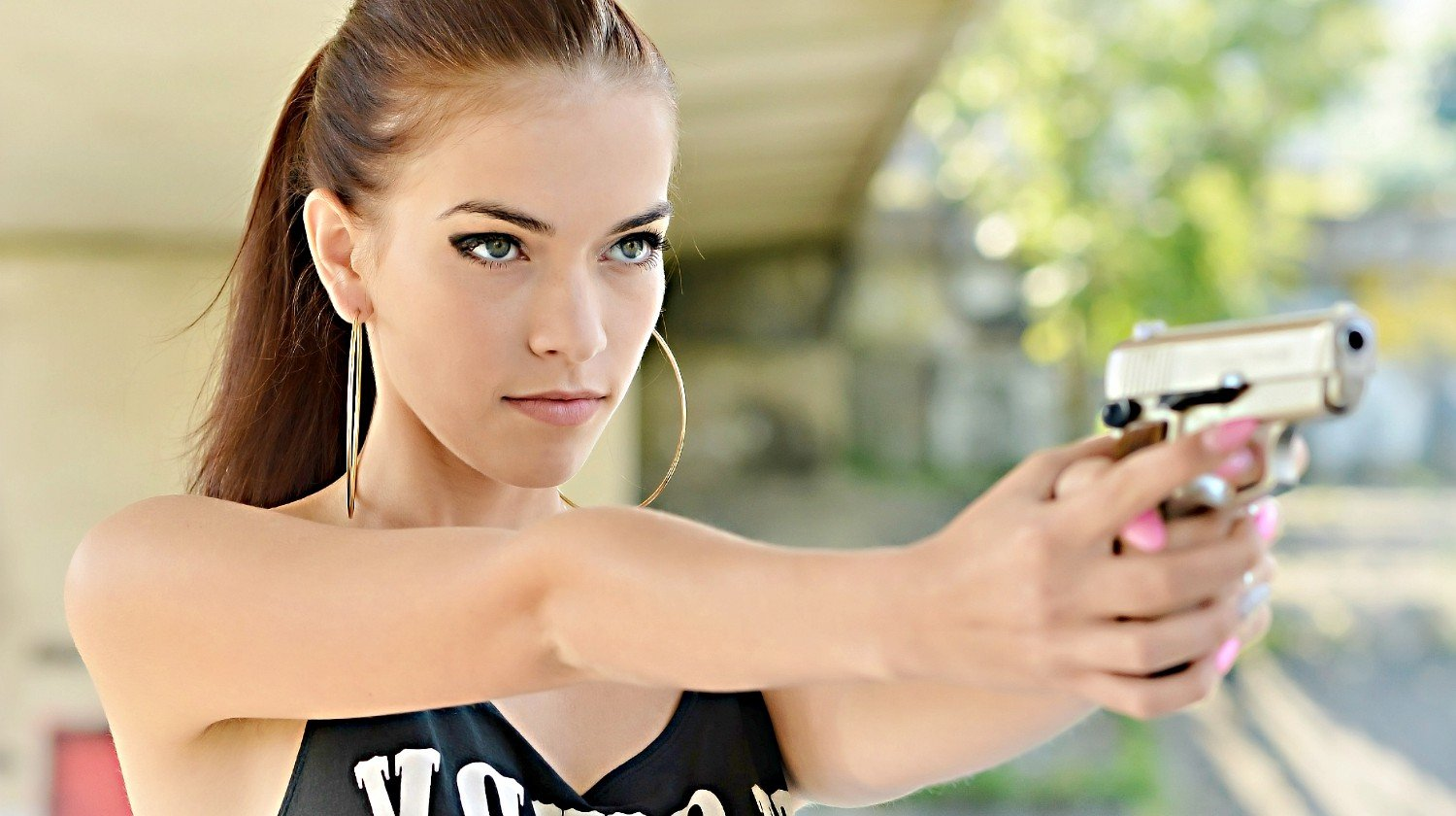 Feature | Beautiful woman with gun | What's The Best Handgun For Women?