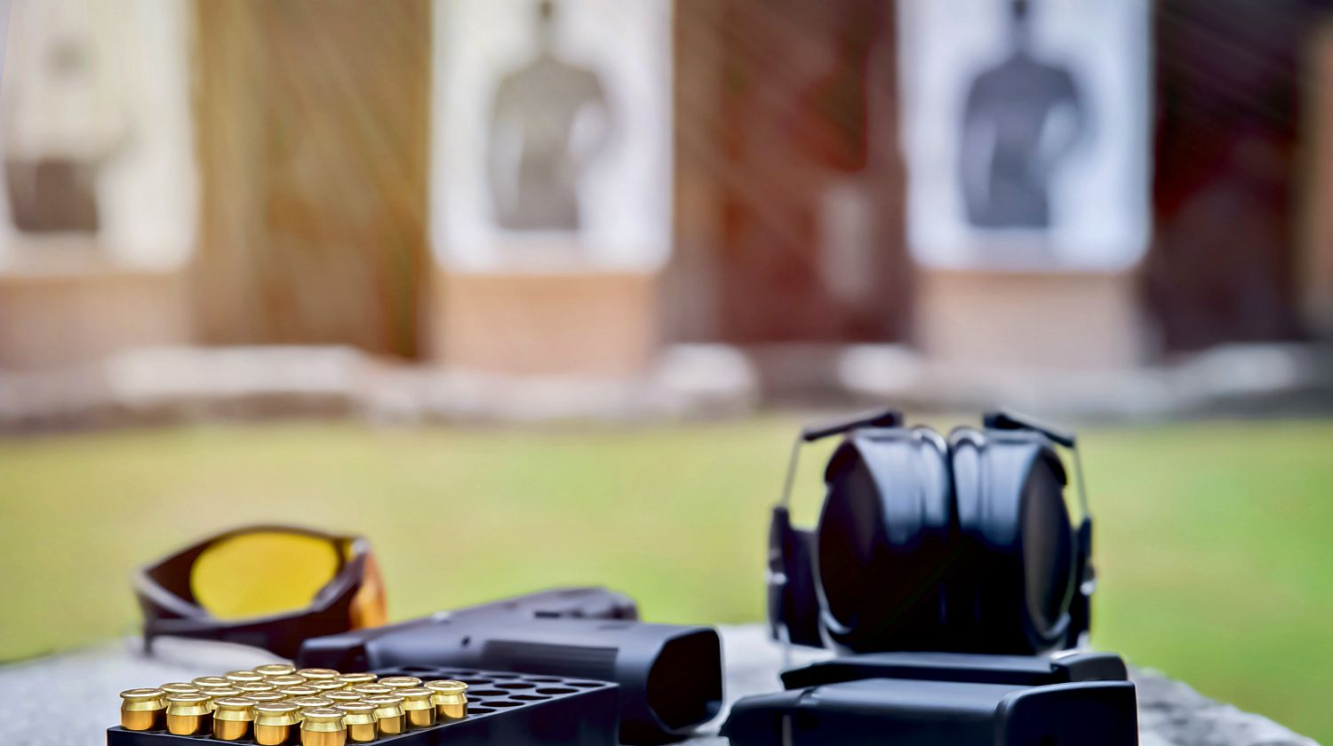 Feature | Gun, bullets, ear plugs and shooting accessories on the table at shooting range | Shooting Fundamentals